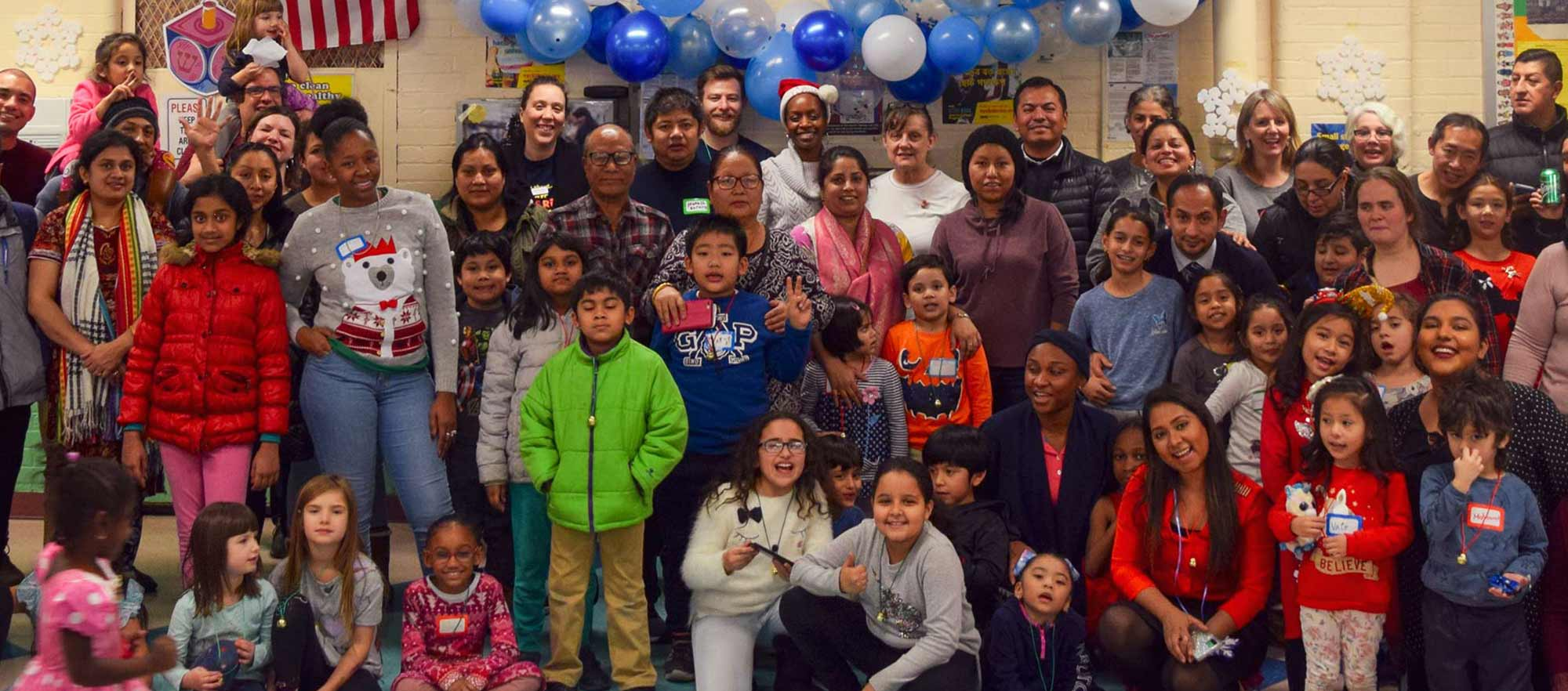 Diverse families gathering at a celebration in a classroom.